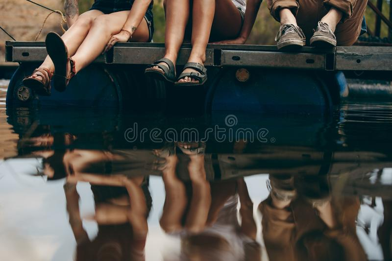 Friends sitting on a floating dock on a lake royalty free stock images