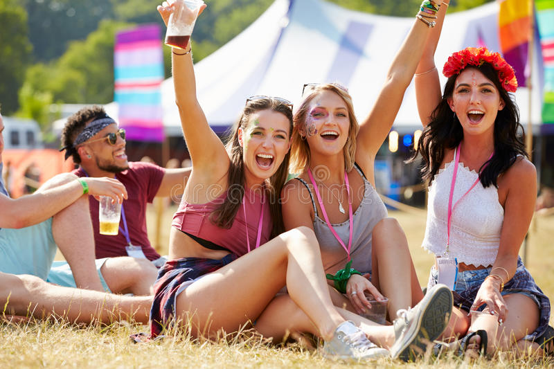 Friends sitting on the grass cheering at a music festival stock image