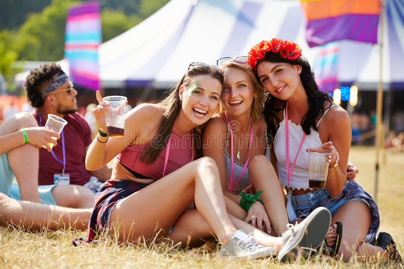 Friends sitting on the grass having fun at a music festival stock images