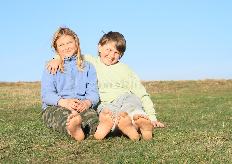 Friends sitting on meadow. Barefoot kids with bare soles - smiling girl and boy sitting on grass of meadow with blue sky behind. Friendship concept royalty free stock photos