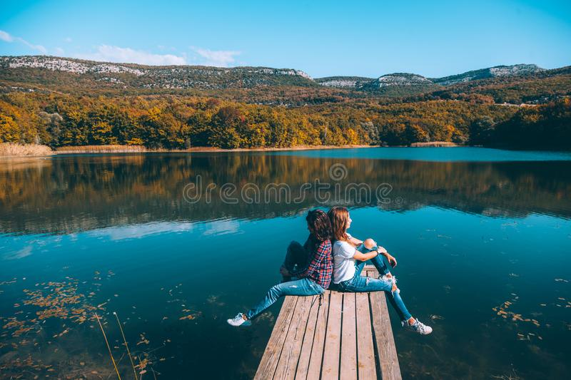 Friends sitting on peer by the lake stock photography