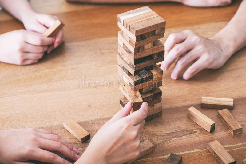 Friends sitting and playing Tumble tower wooden block game together with feeling happy. Friends sitting and playing Tumble tower wooden block game together royalty free stock image