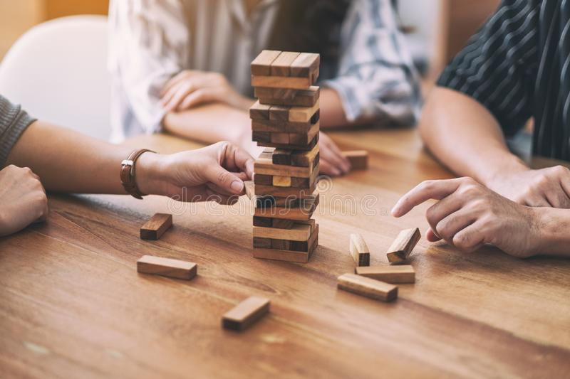 Friends sitting and playing Tumble tower wooden block game together with feeling happy. Friends sitting and playing Tumble tower wooden block game together royalty free stock photo