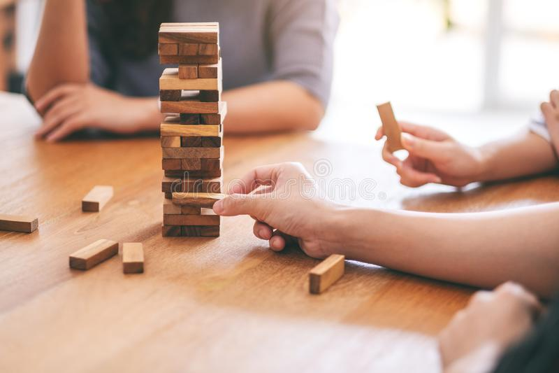 Friends sitting and playing Tumble tower wooden block game together with feeling happy. Friends sitting and playing Tumble tower wooden block game together stock photography