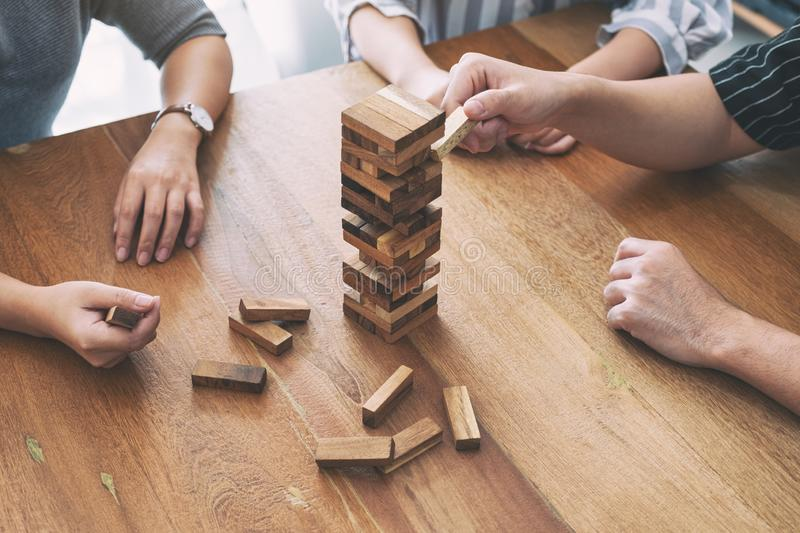 Friends sitting and playing Tumble tower wooden block game together with feeling happy. Friends sitting and playing Tumble tower wooden block game together royalty free stock images