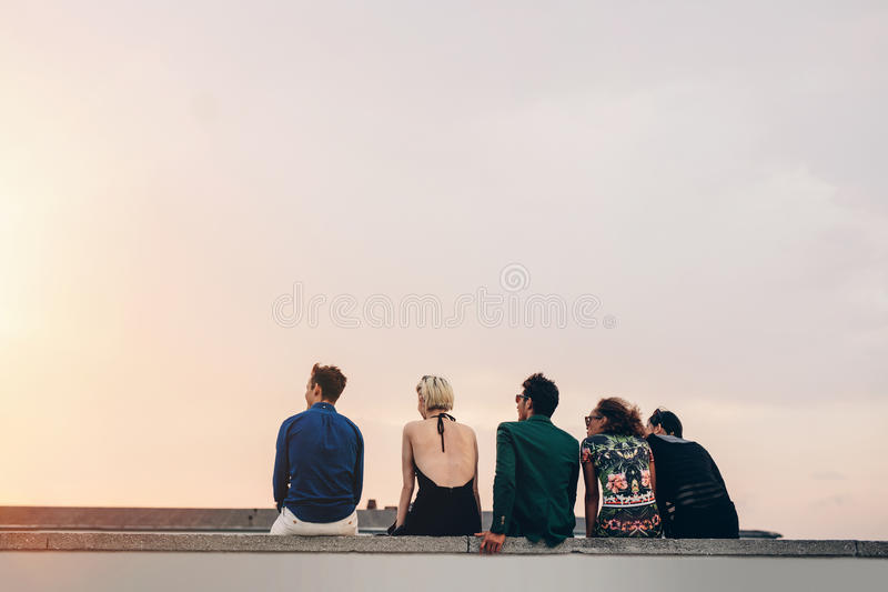 Friends sitting together on rooftop at sunset. Rear view of young friends sitting together on rooftop at sunset. Young men and women hanging out on terrace in stock photos