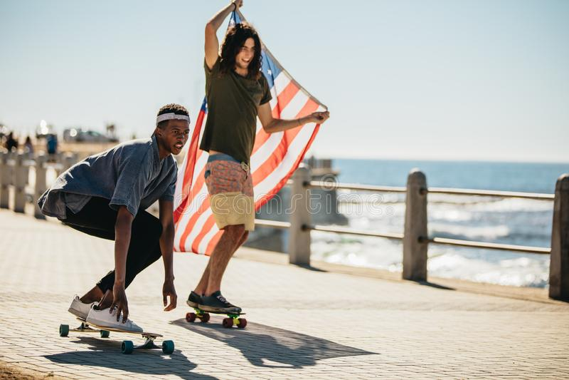 Friends skateboarding on seaside promenade. Two young skateboarder doing skateboarding with USA flag on the road by the beach. Multi-ethnic friends skateboarding stock image