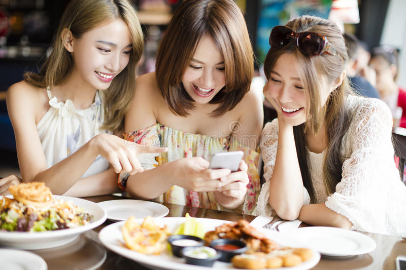 friends with smart phones taking picture in restaurant stock photos