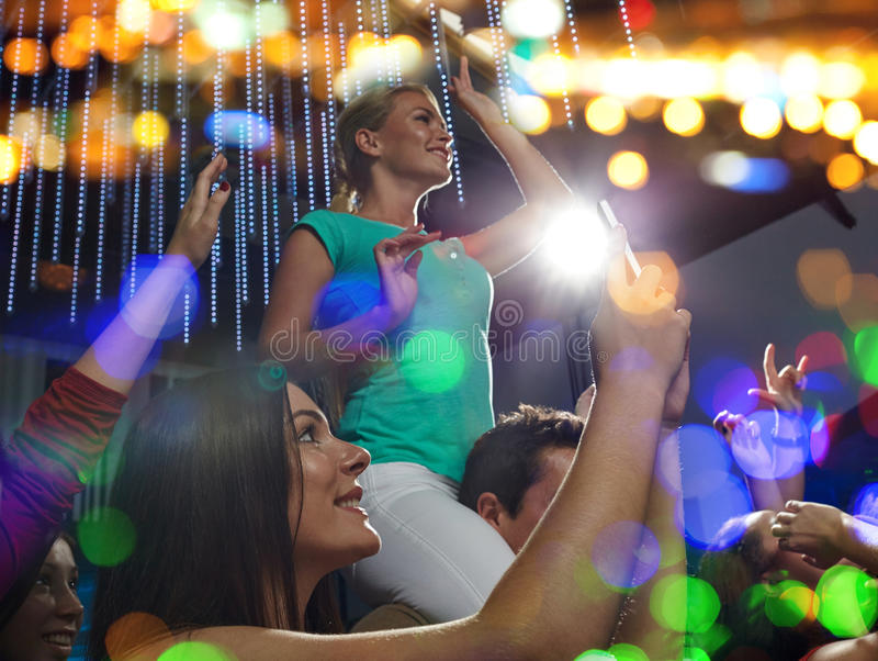 Friends with smartphone taking picture at concert. Party, holidays, celebration, nightlife and people concept - smiling friends with smartphone taking picture stock photography