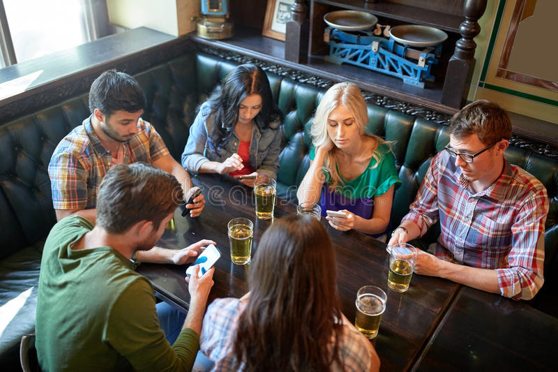 Friends with smartphones and beer at bar or pub. People, leisure, friendship and communication concept - friends with smartphones drinking beer and texting at royalty free stock photo