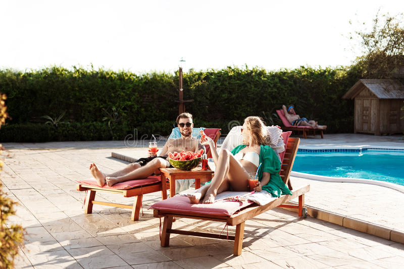 Friends smiling, drinking cocktails, lying on chaises near swimming pool. Young beautiful friends smiling, drinking cocktails, lying on chaises near swimming stock photo