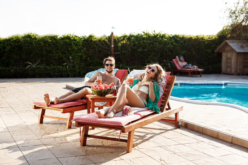 Friends smiling, drinking cocktails, lying on chaises near swimming pool. Young beautiful friends smiling, drinking cocktails, lying on chaises near swimming royalty free stock images