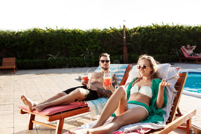 Friends smiling, drinking cocktails, lying on chaises near swimming pool. Young beautiful friends smiling, drinking cocktails, lying on chaises near swimming stock images