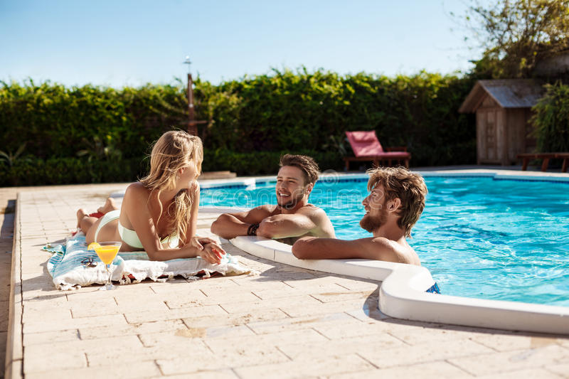 Friends smiling, drinking cocktails, relaxing, sitting near swimming pool. Young beautiful friends smiling, drinking cocktails, relaxing, sitting near swimming royalty free stock image