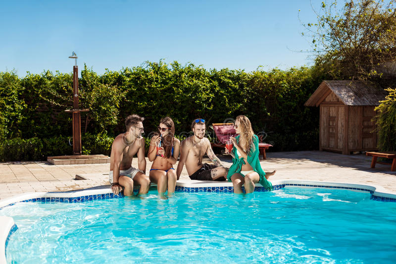 Friends smiling, drinking cocktails, relaxing, sitting near swimming pool. Young beautiful friends smiling, drinking cocktails, relaxing, sitting near swimming royalty free stock images