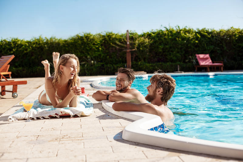 Friends smiling, drinking cocktails, relaxing, sitting near swimming pool. Young beautiful friends smiling, drinking cocktails, relaxing, sitting near swimming royalty free stock photos