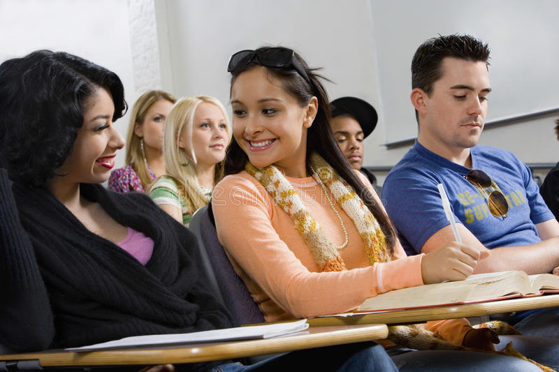 Friends Smiling And Looking At Each Other In Classroom stock images
