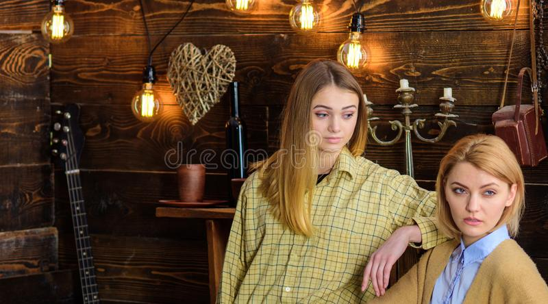 Friends spend pleasant evening in gamekeepers house, interior background. Girls on calm faces enjoy warm atmosphere. While having rest. Two friends meeting royalty free stock photography