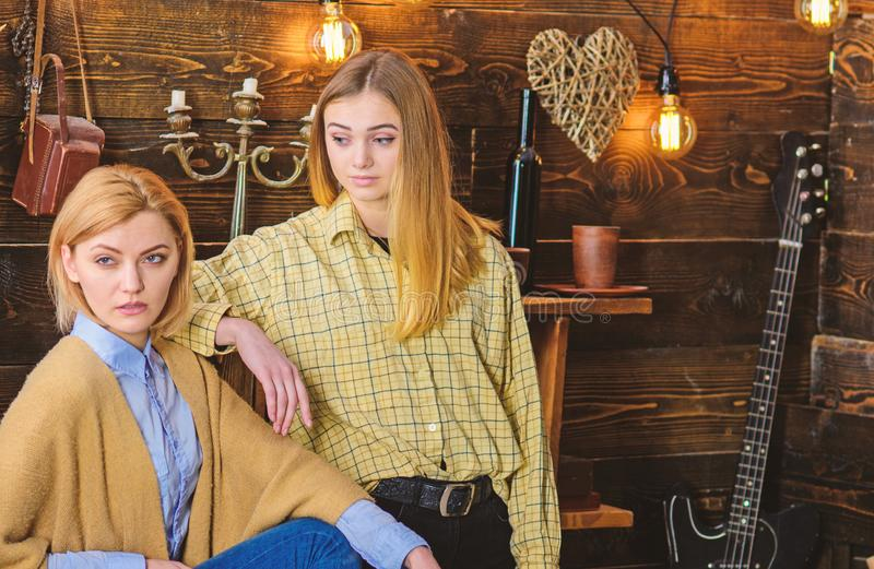 Friends spend pleasant evening in gamekeepers house, interior background. Girls on calm faces enjoy warm atmosphere. While having rest. Two friends meeting stock photography