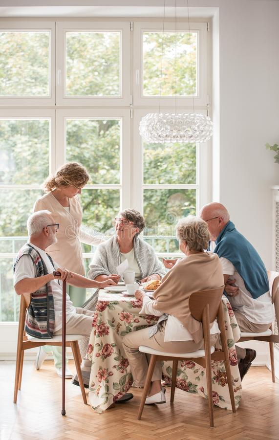 Elderly friends spending time together by drinking tea and enjoying photos in common dining room of nursing home stock photography