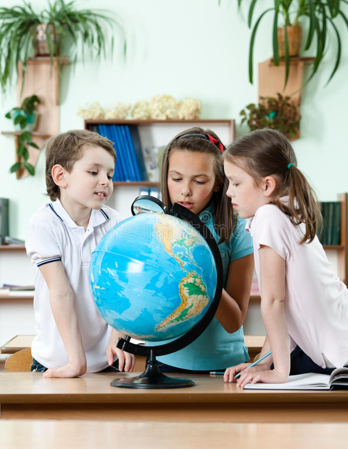 Friends stare at school globe stock photography