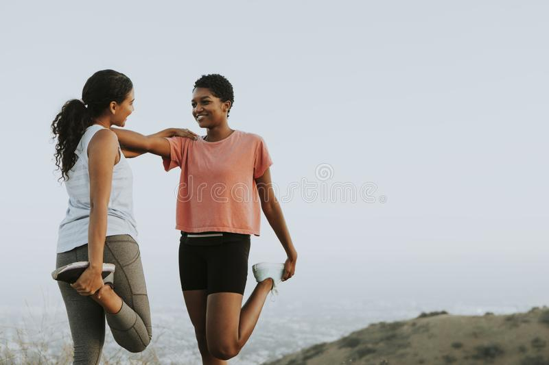 Friends stretching together while on a hike stock photography