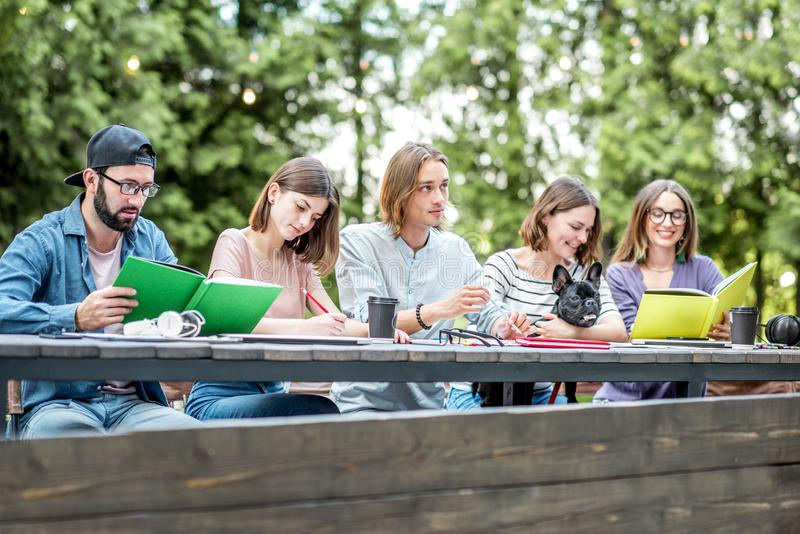Friends studying outdoors. Young friends dressed casually studying with colorful books sitting in a row at the table outdoors royalty free stock image