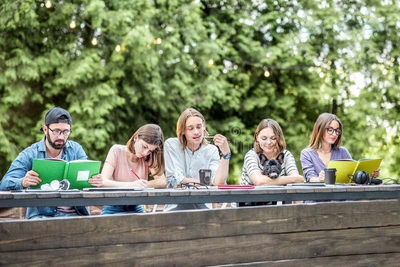 Friends studying outdoors. Young friends dressed casually studying with colorful books sitting in a row at the table outdoors stock photo