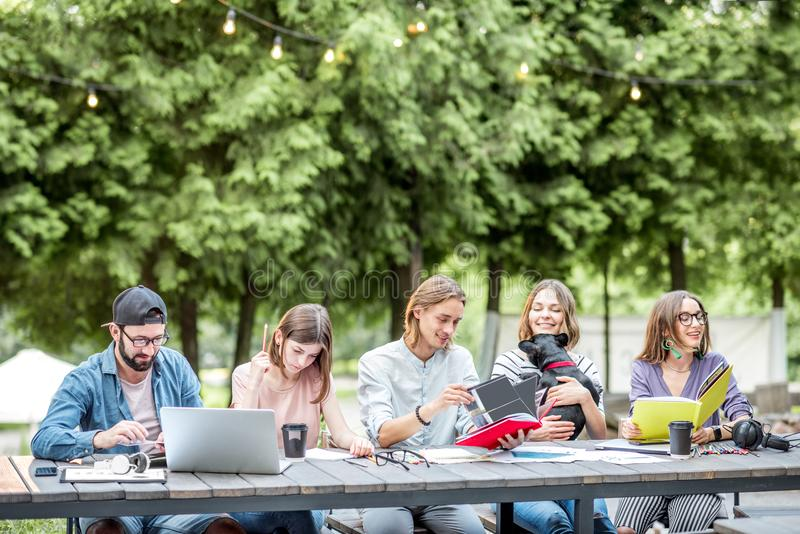 Friends studying outdoors. Young friends dressed casually studying with colorful books sitting in a row at the table outdoors stock photography