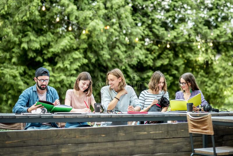 Friends studying outdoors. Young friends dressed casually studying with colorful books sitting in a row at the table outdoors stock photos