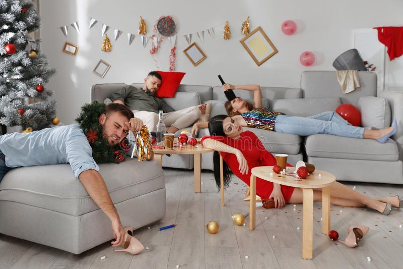 Friends suffering from hangover in room after New Year party stock photography