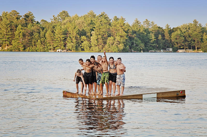 Friends at summer camp. A group of nine kids ages 11-13 on a floating dock in a lake at sumer camp royalty free stock image