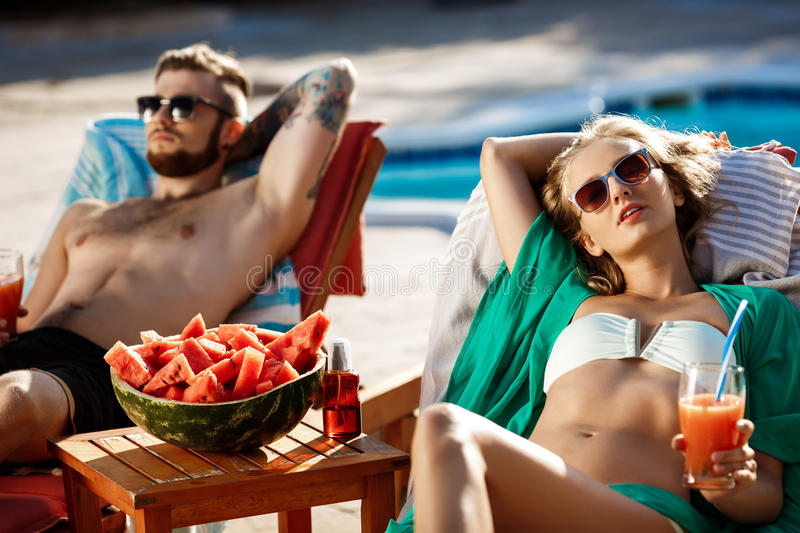 Friends sunbathing, drinking cocktails, lying on chaises near swimming pool. Copy space royalty free stock photos