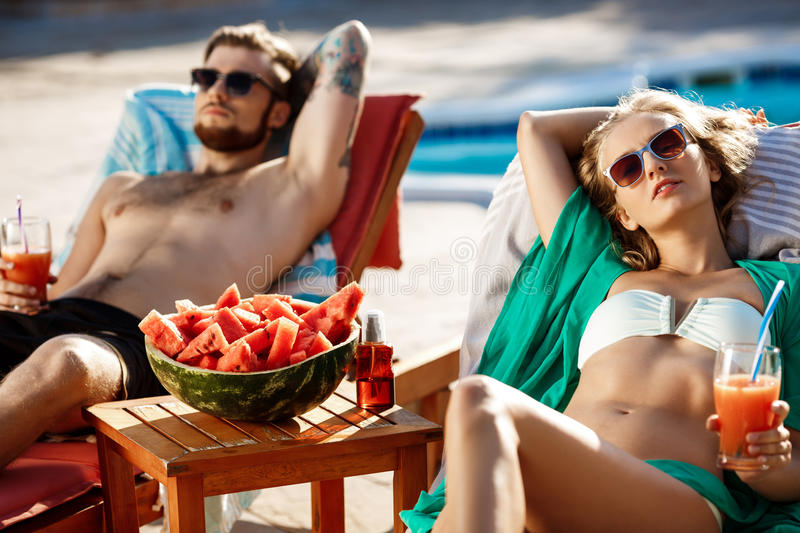 Friends sunbathing, drinking cocktails, lying on chaises near swimming pool. Copy space stock image