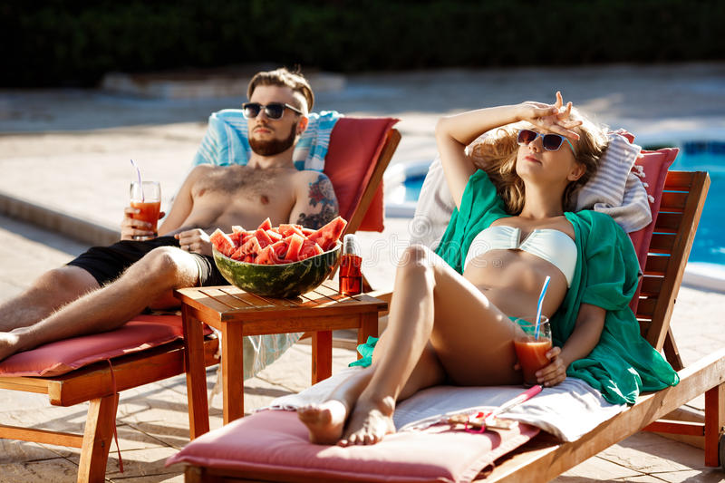 Friends sunbathing, drinking cocktails, lying on chaises near swimming pool. Copy space royalty free stock photography