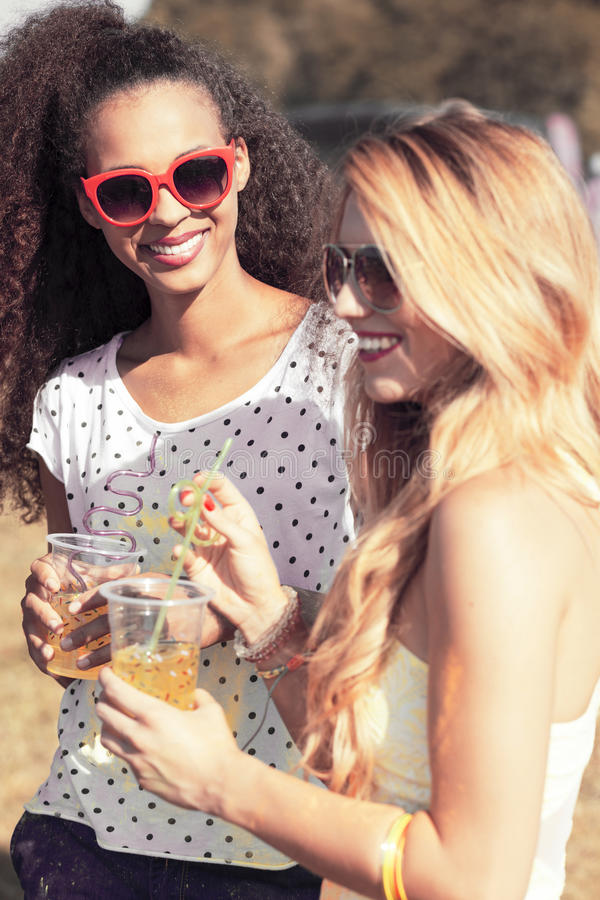 Friends in sunglasses holding beers. Two young friends in sunglasses holding beers, relaxing in the fresh air royalty free stock image