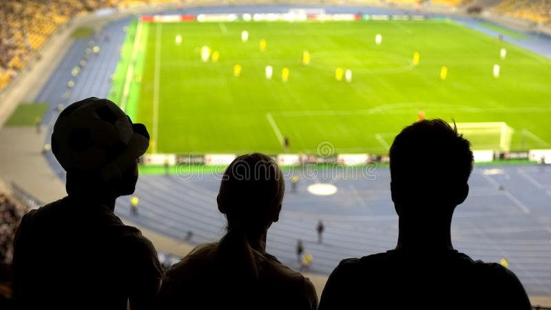 Friends supporting soccer team, watching football match at stadium, sports royalty free stock photo
