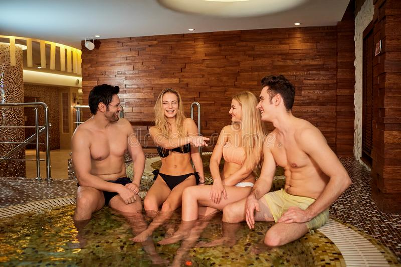 Friends in swimsuits laugh at the jacuzzi in the spa center. royalty free stock photography