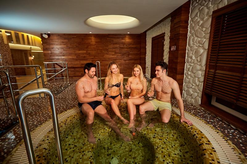 Friends in swimsuits laugh at the jacuzzi in the spa center. royalty free stock photos