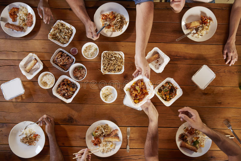 Friends at a table sharing Chinese take-away, overhead view royalty free stock photography