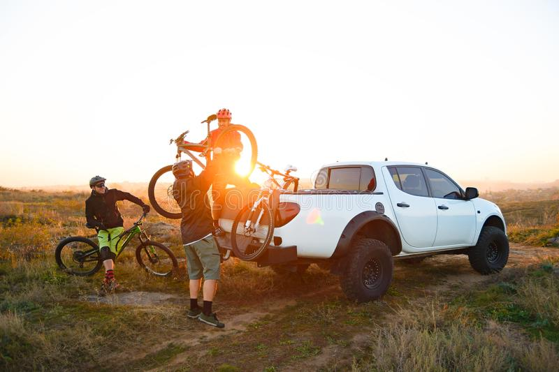 Friends Taking MTB Bikes off the Pickup Offroad Truck in Mountains at Sunset. Adventure and Travel Concept. Friends Cyclists Getting Ready for Bike Riding and royalty free stock photos