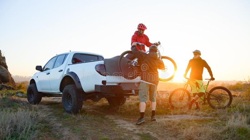 Friends Taking MTB Bikes off the Pickup Offroad Truck in Mountains at Sunset. Adventure and Travel Concept. Friends Cyclists Getting Ready for Bike Riding and stock photography