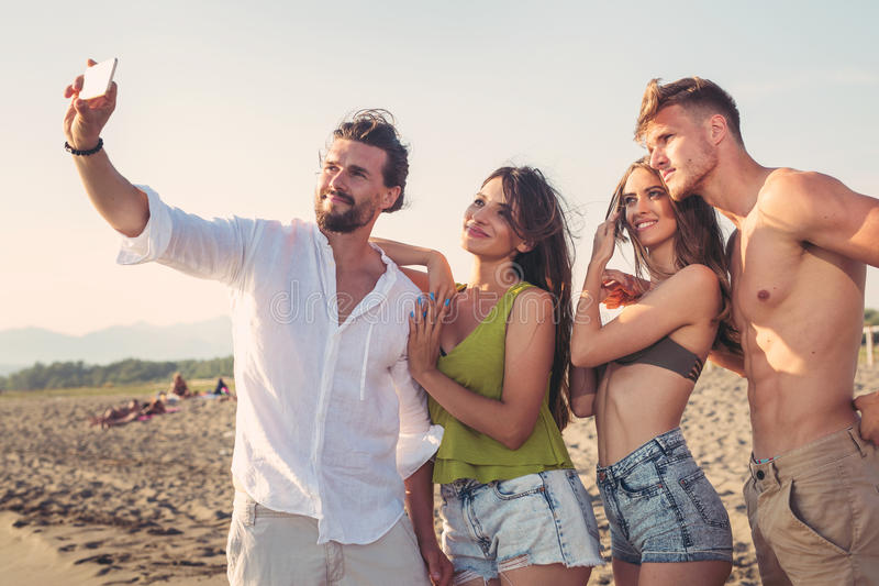 Friends taking selfie at beach on sunny day stock images