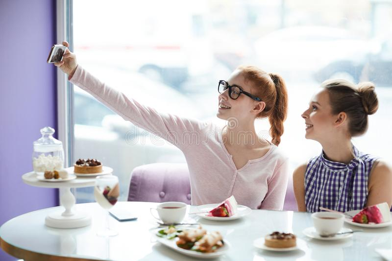 Friends taking selfie in cafe royalty free stock image