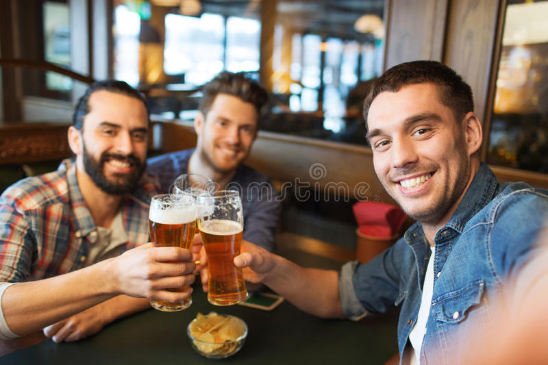 Friends taking selfie and drinking beer at bar stock photo