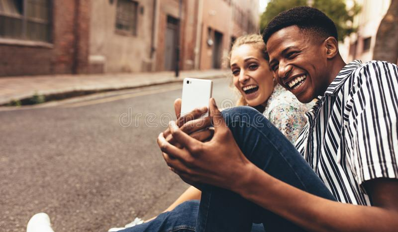 Friends taking selfie. Man taking selfie with his female friend sitting outside by the street. Cheerful friends making a selfie outdoors royalty free stock photos