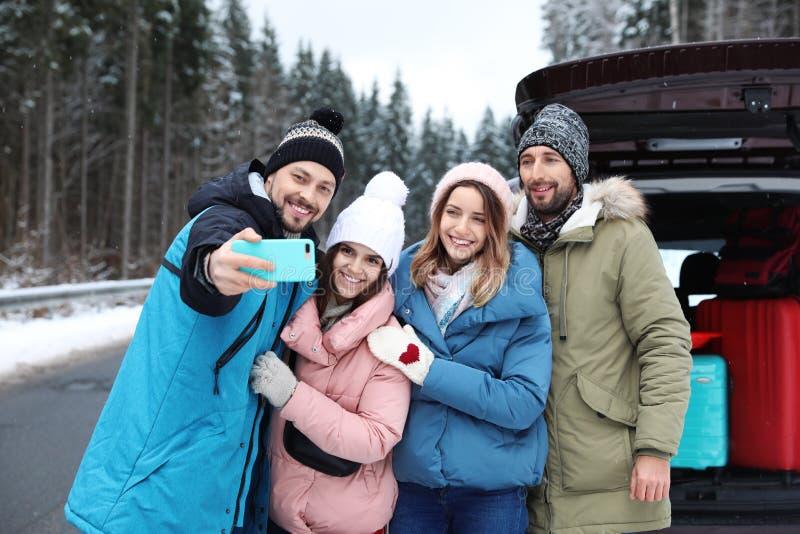 Friends taking selfie near open car trunk on road. stock photos