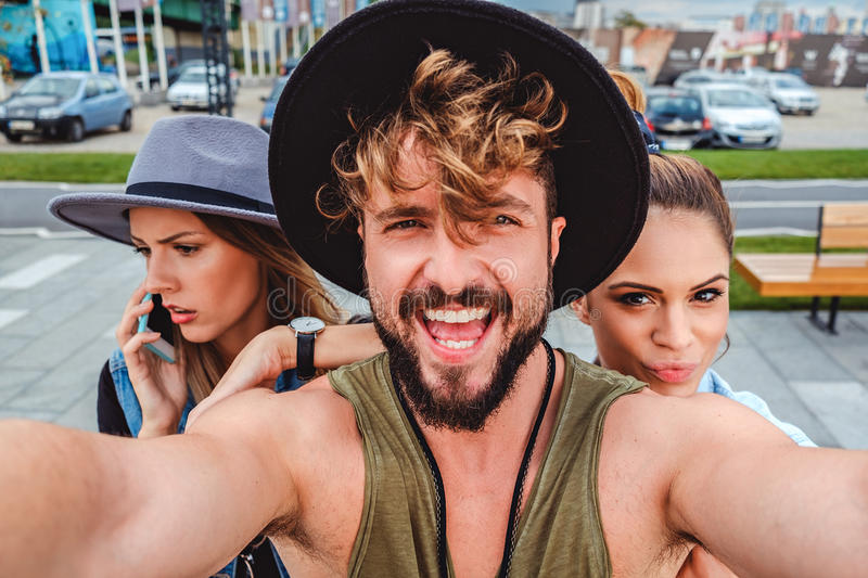 Friends taking selfie and one talking on the phone. Summertime stock images
