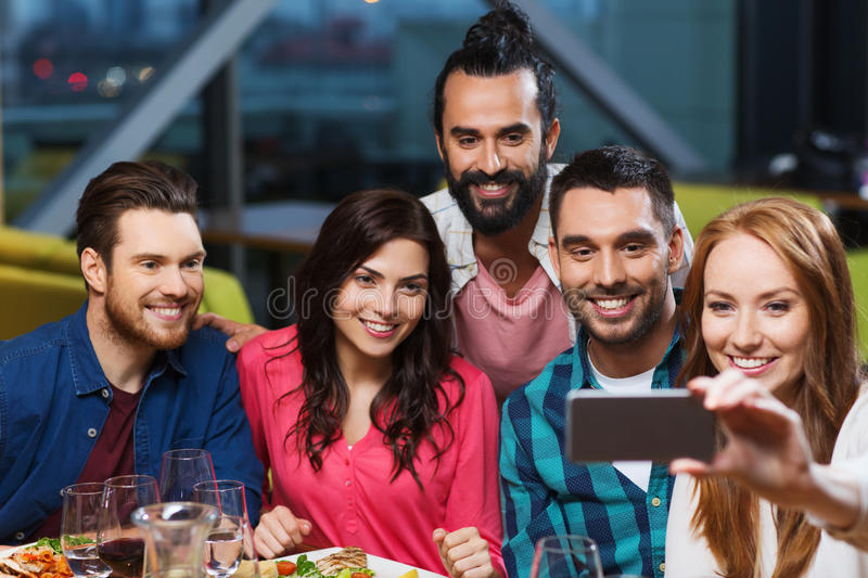 Friends taking selfie by smartphone at restaurant royalty free stock images