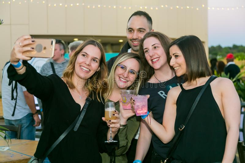 Friends taking a selfie on their phone and generally enjoying a day out at a Food and Wine Fair stock photos